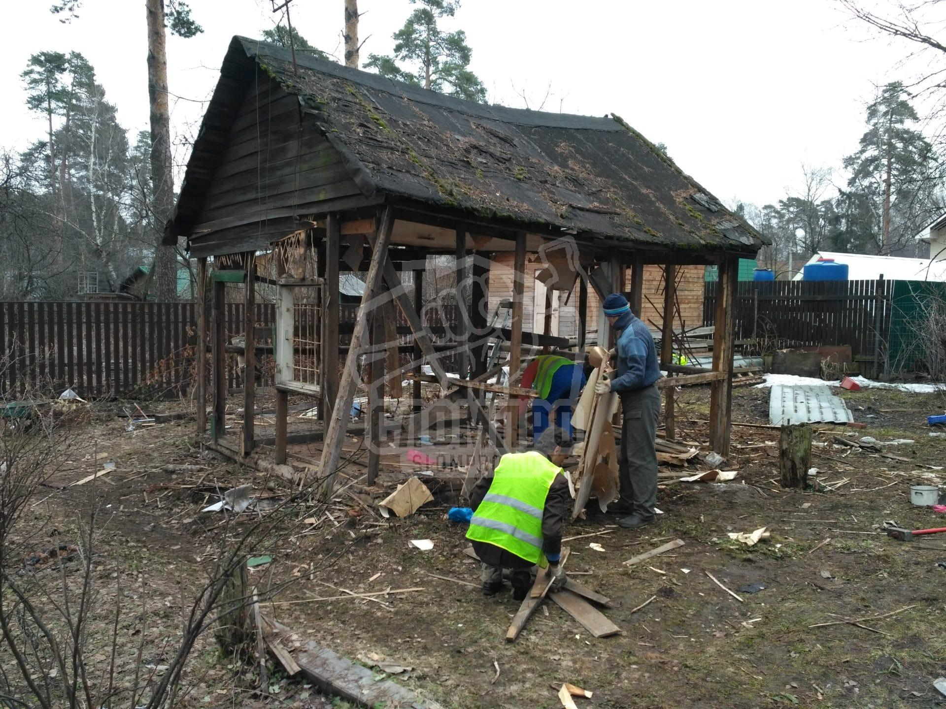 Процесс демонтажа стен сарая для дальнейшего заваливания
