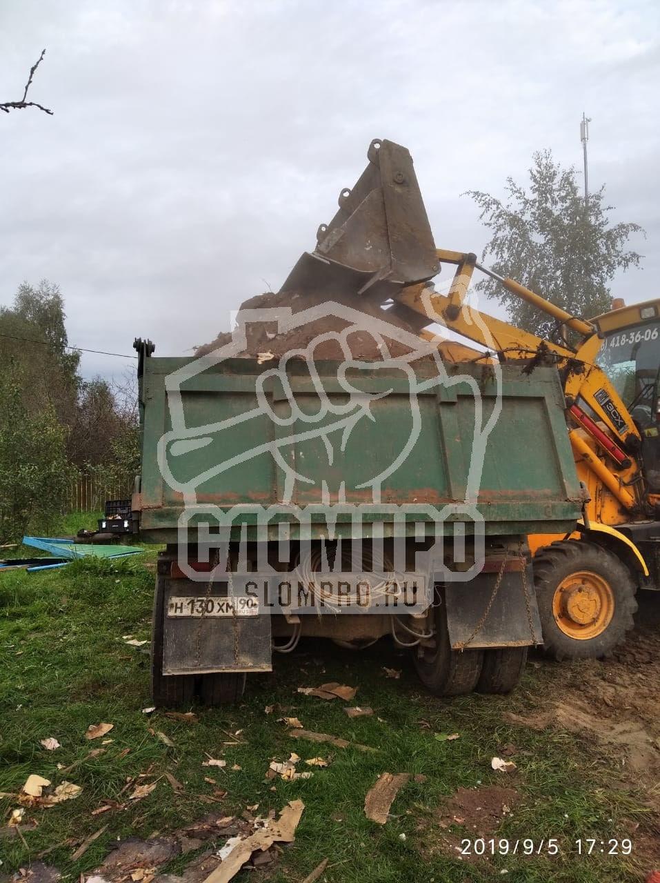 Погрузка строительного мусора в самосвал.