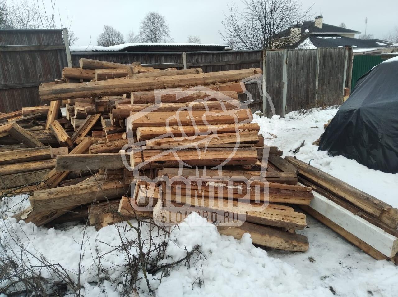 Складированные деревянные бревна после демонтажа дома